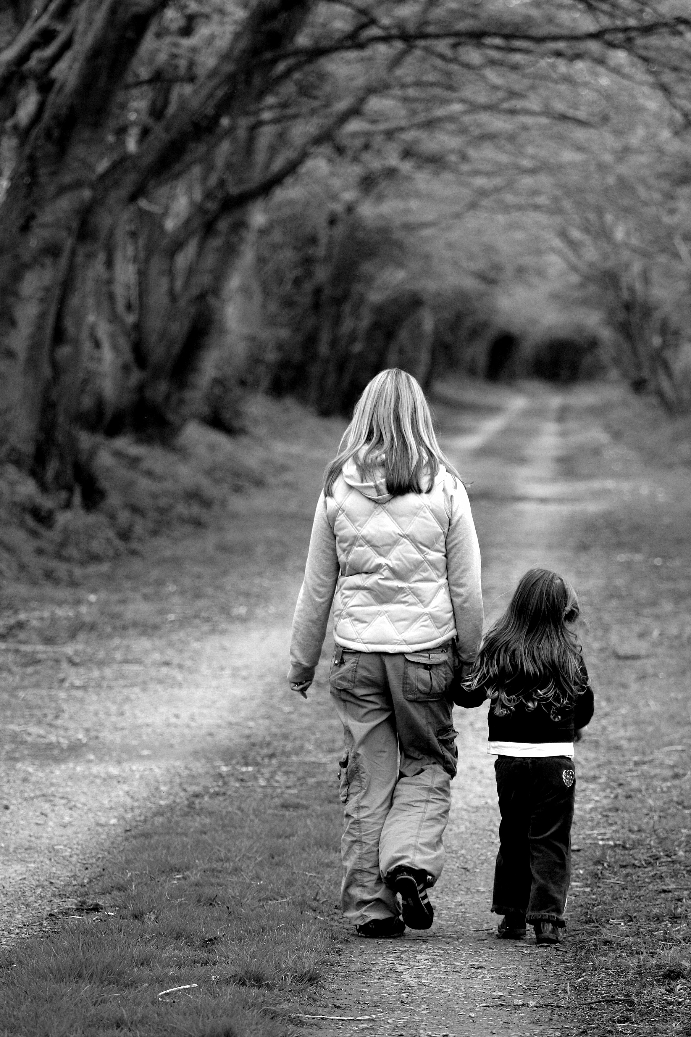 mom and daughter walking down road black and white pic