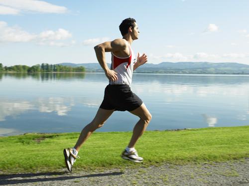 Guy running next to lake