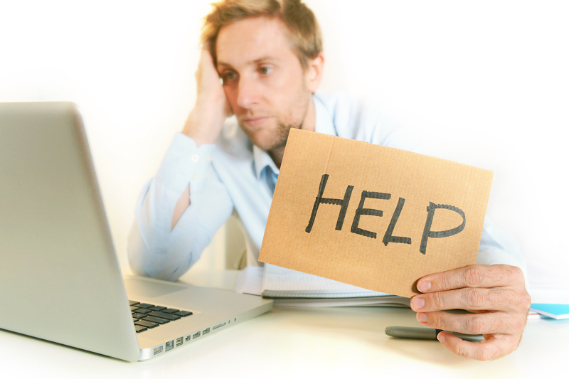 guy at computer with help sign